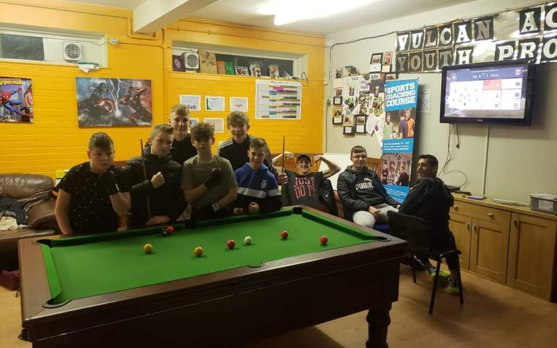 Young men gather around a pool table